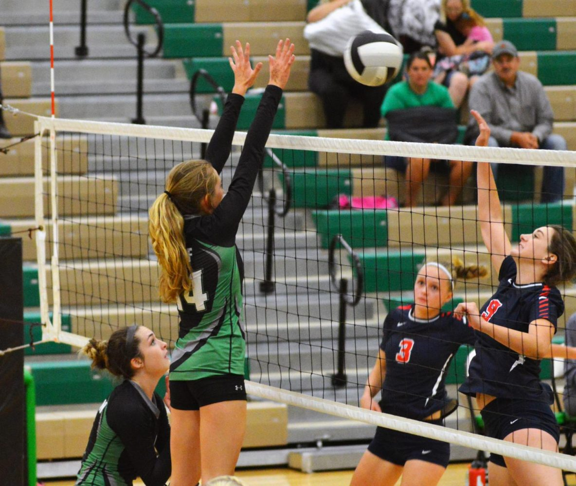 NET ACTION. Kaitlyn Neff (11) jumps to block the ball.