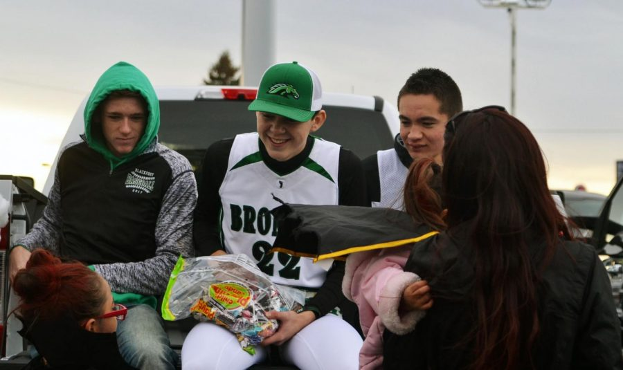 SWOOSH.  Basketball Players Cayden Cornell(11), Trevor  Miller(12), and Dylan Fuller(12) converse with a trick or treater.