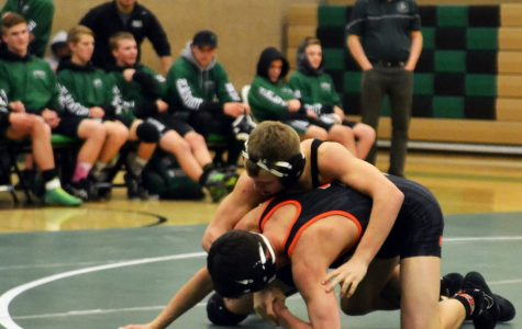 Rich Moore (9) does a  take down on a wrestler from Idaho Falls.