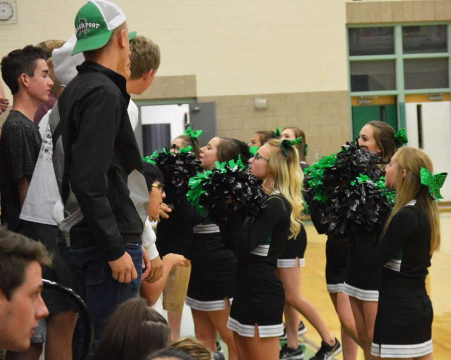 Cheerleaders leading the student section through a cheer