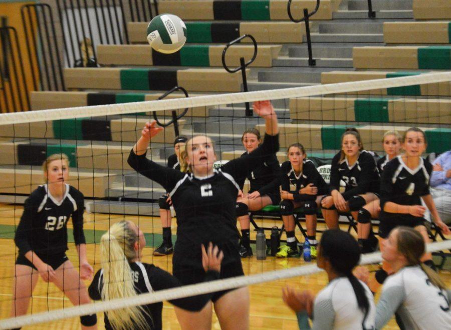Michaela Eldredge (12) hitting the ball over the net to the opposing team