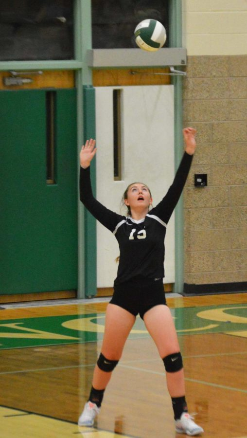 Emalee Evans (12) serving the ball over to opposing team