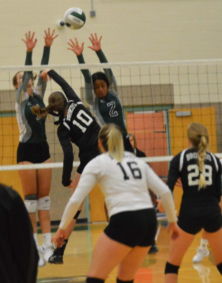 Hannah Hirschi (11) hitting the ball over the net just as the opponents miss the block