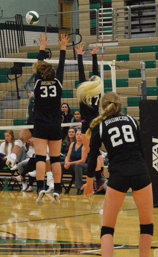 Josie Anderson (12) and Hadley Humpherys (9) mid-air blocking the ball