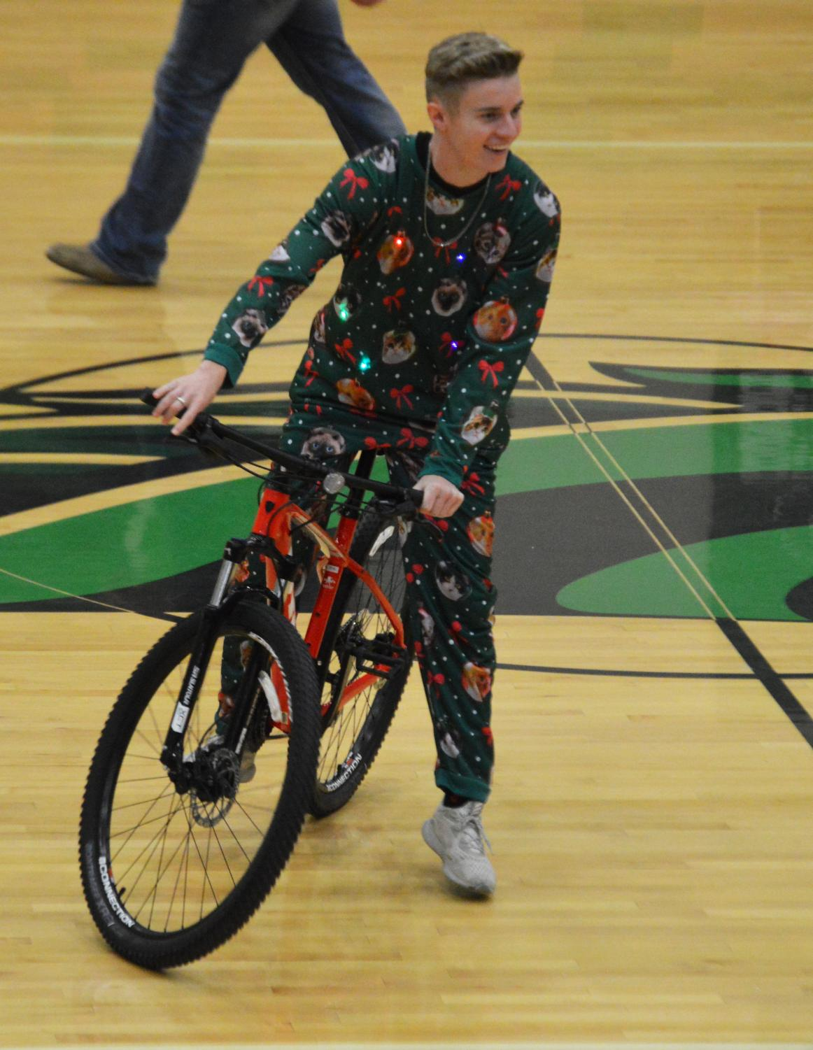 Nephi Bigler (12) showing off a bike that was auctioned off.