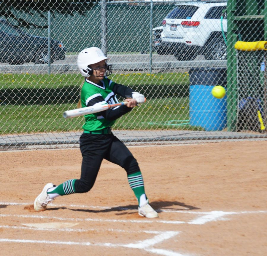 HIGH INSIDE. Ahna Yancey(12) swings at a high ball and sends it sailing