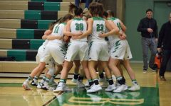 B-R-O-N-C-O-S. The girls' varsity basketball team huddles up for a cheer before warming up.