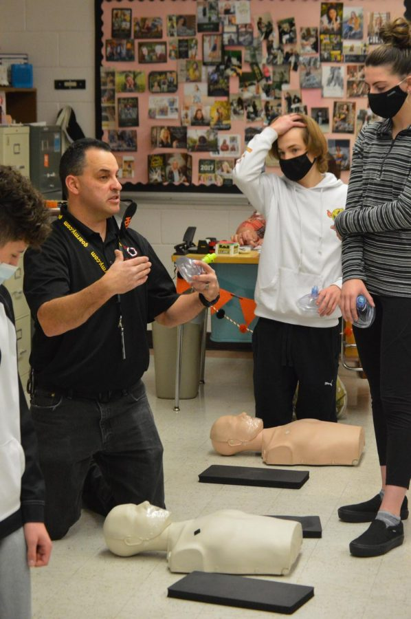 Jack day (white) and Baylee Whitney (gray) listen to an ISU CPR instructor in Mrs. Colliers CNA class.