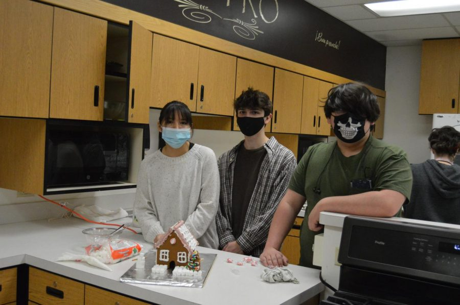 Claire Edmo(left), Jayden Luna (middle), Gabe Christiansen (right) pose for a picture with their gingerbread house they made in Mrs. Lukers culinary class